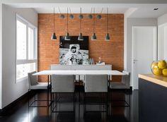 A sala de jantar ganhou uma parede revestida com tijolos Pasinato. Mesa de jantar e cadeiras da Carbono Design. O buffet foi desenhado pelo escritório Drops e executado pela REM Marcenaria. Luminárias à venda na Reka (Foto: Julia Ribeiro/Divulgação)