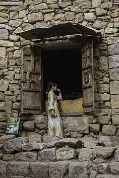 Girl buying Girl (a quality ghee butter) at a shop in the Haraz mountains of Yemen by Phil Marion