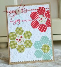 http://scrapbookgirl.typepad.com  I used my Cricut along with the Accent Essentials cartridge to cut a bunch of hexagons from different patterned papers.  I arranged them into flower clusters on top of an embossed background which reminded me of a piece of fresh cotton fabric.  A simple stamped sentiment and a bit of baker's twine finish off the country cottage look.