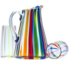 """For its Canne collection, the artisans at the Murano firm Cenedese fuse colored glass rods before blowing each piece. The 9""""-h. pitcher is $665, and the 5""""-h. glasses are $150 each."""