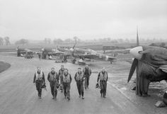 """Pilots of No. 245 Squadron RAF walk past their Hawker Typhoon IBs to their dispersal hut at Westhampnett, Sussex, on completion of a sortie against a flying-bomb launching site (codenamed """"Noball"""") in northern France. Three of the Typhoons wear cowling covers with """"chimneys"""" for the insertion of a heater, in order to aid the engine start. In the background is a Hawker Hurricane, used by the Squadron as a communications and training aircraft"""