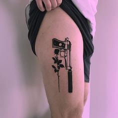 Solid black tattoo of a pistol with a silencer inked on the right thigh