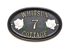 A small oval cottage sign with white classic English Roses motifs.