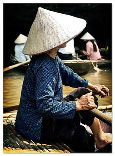 Vietnamese women rowing boats on a river, wearing the characteristic Vietnamese conical hats.