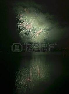 Coloridos fuegos artificiales en el cielo de fondo negro con reflejos en el agua…