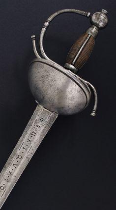 """h79bz2.- Espada """"DE BOCA DE CABALLO"""" para oficial de Caballería. España, mediados siglo XVIII. Guarnición en hierro, formada por doble concha asimétrica, aro guardamano y dos gavilanes vueltos en sentidos opuestos. Del centro surgen los bigotes hasta el plano interior de la guarda. Pomo con perilla. Hoja recta, recazo punzonado, vaceo en su primer cuarto marcado """"EN ALAMANIA – ENRIQUE COEL"""", el resto a tres mesas hasta la punta. Long. total 111 cm: long. hoja 93,5 cm, anch. base hoja 37 mm."""
