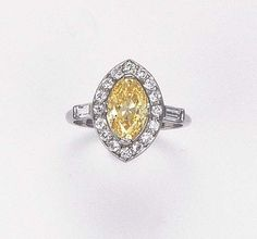 A YELLOW DIAMOND AND DIAMOND CLUSTER RING  The marquise-cut yellow diamond weighing 2.11 carats within brilliant-cut diamond surround to the baguette-cut shoulders and plain hoop