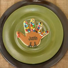 Thanksgiving kids table setting - Love the brown plate with the smaller green one on top! & a cookie for the name card is such a cute idea!