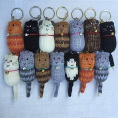 Made to order keyring, featuring a sweet little knitted cat in a variety of colours, complete with wool collar and tiny bell. Embroidered features make each little character unique. These keyrings fit our Hand Printed Cat Gift Boxes perfectly, making them lovely gifts for any cat lover. Gold or silver coloured bell and keychain. Message us if you have a collar colour preference! Dimensions Approx: 10 x 3.5cm