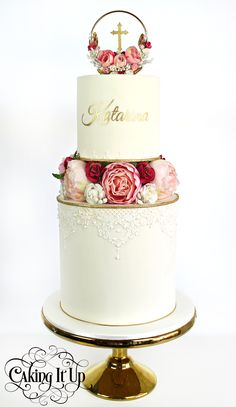 2 tier Christening cake featuring a pretty floral hedging and a matching floral wreath topper.  Embellished  with edible lace, gold trim and hand printed name  www.facebook.com/cakingitup
