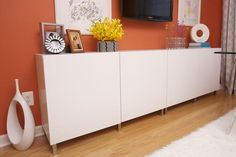 This white modern credenza is a simple design accented by the unique pieces of art mounted above it. A bright coral wall makes the white credenza pop from the background. Art, personal pictures and bright yellow flowers personalize the space. Home Office Storage, Home Office Space, Home Office Decor, Home Decor, Office Spaces, Credenza Decor, White Credenza, Modern Credenza, Eclectic Living Room