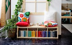 a window seat made from shelving with pillows on top. Great for storing extra media