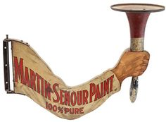 """""""Martin-Senour Paint"""" sign and display in the form of an arm and brush, painted wood, with hand holding a house painting brush, supports a metal tray that holds a paint can (not shown). It has great color and lettering and a realistic rendering of the hand. It came with a dummy paint can with a label for """"Ro-So Lite"""" by Rosenbush and Solomon. This 17"""" wide sign, with some spotting and damage, sold for $9200 (est. $800/1200) to Oliver Clark. Bill Powell collection."""