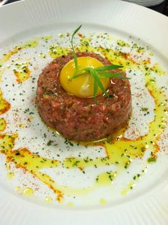 Steak tartare of filet mignon cryo-poached and pureed with shallots and cryo-shattered tarragon and chives, served with a ducks egg yolk and smoked paprika
