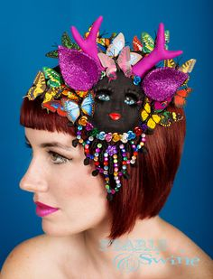 The Butterfly Catcher – Dollface Antler Fascinator #Unique black #doll faced #headpiece with pink #glitter ears, pink #handmade #antlers, long black #eyelashes and many #butterflies. Decorated with lace covered in multicoloured gems. She can be hung on the wall as a piece of art too! One of a kind. http://www.pearlsandswine.com