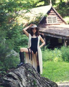 Posing outdoors, Rachel Weisz wears Elizabeth and James cardigan, Eres swimsuit and Saint Laurent boots