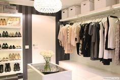 Clean, modern closet with glass top island, custom shoe wall, striped black on black wallpaper with great light fixture!