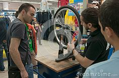 Mechanic teaching people how to true a bike wheel on a truing stand at a bicycle repair workshop in Decathlon store. http://www.dreamstime.com/editorial-image-mechanic-teaching-people-how-to-true-bike-wheel-truing-stand-bicycle-repair-workshop-decathlon-store-image47749015