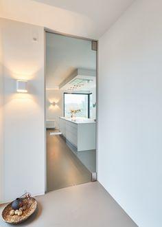 Glazen binnendeur van vloer tot plafond, goed afsluitend door de minimalistische omlijsting met ingebouwde afdichting. Er dient niets in de vloer bevestigd te worden! #glazendeur