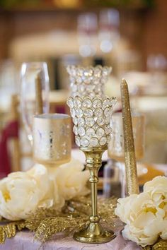 Mercury glass, glittery candles, and crystal tea lights are set off by glistening foliage and cream-colored floral accents in a dazzling tablescape. #weddingplanning #planitevents #weddingdecor #gold #glitter #glam #shimmer