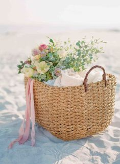 basket on a beach with towels and flowers http://itgirlweddings.com/seaside-bridal-shower/