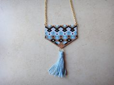 A beaded necklace with delica seed beads and a handmade tassel. The length of the necklace is adjustable (+ 6cm extension chain).  The colors of the beaded part are: black, white, light blue and gold and the color of the chain is gold. The handmade tassel is in light blue. (Please note that colors may appear differently in different screens).  For any request on different color or length, do not hesitate to contact us.  Add a boho chic attidute to your outfits with this amazing necklace.