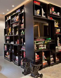 A caixa cinza e neutra destaca o acervo do proprietário, incluindo diversas peças de toy art do apartamento