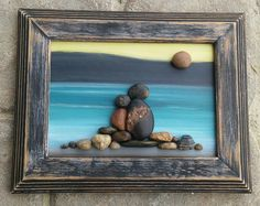 "Pebble Art Couple in the outdoors surrounded by the mountains and water under a sun in a 5x7 ""open"" wood frame"