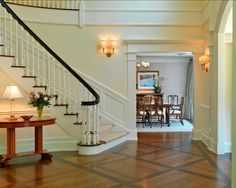 This entryway feels traditional and timeless. I also love the custom wood floor design.