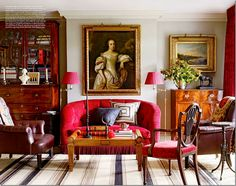 lovely room: red tufted and fringed sofa, leather chair, antique coffee table and chairs, striped blue rug, portrait--wonderful mix