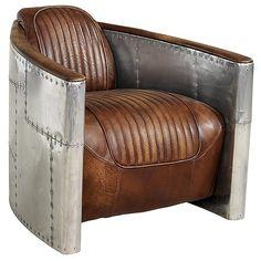 Original sillón de cuero envuelto en aluminio. Su diseñador Timothy Oulton se ha inspirado en el avión Grumman F-14 Tomcat. Las curvas aerodinámicas de la silla rinden homenaje al diseño del ala y están revestidas en aluminio, mientras que el asiento y la parte trasera están tapizados con piel ribeteada similar a las chaquetas bomber. Su asiento bajo y el respaldo ligeramente inclinado hacia atrás le dan ese toque arrogante de los aviadores. $2.574,00 €