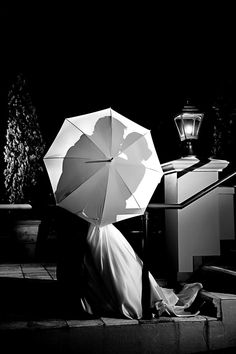 Black and white photo - silhouette of bride and groom kissing behind umbrella - photo by South Africa based wedding photographer