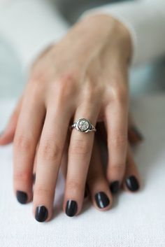 The Anastasia ring is a Vintage Engagement Ring from the Art Deco era circa 1925! This two-tone beauty centers an old European cut diamond weighing approximately 1.01 carats of J-K color, SI2 clarity. The diamond is set in a platinum bezel with a concentric platinum halo. To each side is a small diamond set in platinum and decorated with millegrain