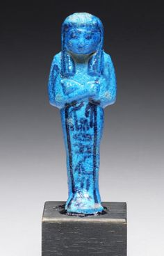 An Egyptian bright blue glazed composition shabti for Tayuheret  Third Intermediate Period, 21st Dynasty, circa 1069-945 B.C. With details in black, holding two hoes, wearing a broad collar and striped tripartite wig, with a single column of hieroglyphs at the front, a large seed-bag with loops slung across the back, 4¼in (10.5cm) high, mounted