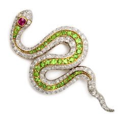 Diamond and green garnet slithering snake brooch, set in platinum and gold, and with a ruby-set head.    American, ca. 1900  Length: 2-1/4 inches
