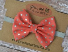 Coral & Silver Bow Headband; Coral color fabric bow with metallic silver polka dots on a silver elastic headband; baby bow headband