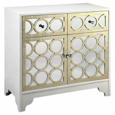 "2-door hand-painted mirrored cabinet with 2 drawers and gold-hued lattice overlay.  Product: CabinetConstruction Material: MDF and mirrored glassColor: White and goldFeatures: Two drawers and two doorsDimensions: 31.5"" H x 31.75"" W x 16"" D"