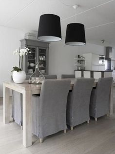 grey linen slip covered dining chairs and palest blonde woods in a pretty white dining/kitchen