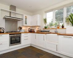 photo of classic modern white kitchen with belfast sink stainless steel splashback