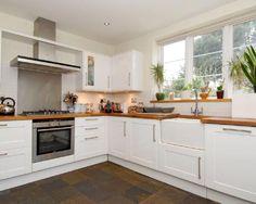 photo of classic modern white kitchen with belfast sink stainless steel splashback