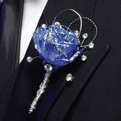 Silver on a blue rose boutonniere with lots of bling