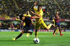 Pedro Rodriguez of FC Barcelona duels for the ball with Javier Aquino of Villarreal CF during the La Liga match between Villarreal CF and FC Barcelona at El Madrigal on April 27, 2014 in Villarreal, Spain.
