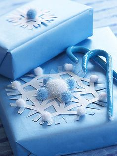 Snowflake Present Topper  Embellish plain gift wrap with these frosty accents. Cut two snowflakes: one from white paper and one from pale blue paper. Layer the snowflakes and adhere to a wrapped package using a glue stick. Hot-glue white and blue pom-poms to different snowflake tips to add dimension.