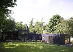 This 1960s house outside London has been renovated to create a modern home that features black-painted brickwork, large windows and a new angular roof.
