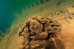 """Es war im Jahr 2001, als Taucher im Qiandao-See etwa 30 Meter unter der Oberfläche auf etwas stießen, das ihnen den Atem stocken ließ: Kunstvoll verzierte Häuser, Stadttore und Mauern erhoben sich auf dem Seegrund, verteilt über ein riesiges Areal. Was sie entdeckt hatten, war die vor mehr als 40 Jahren versunkene und in Vergessenheit geratene Stadt Shi Cheng (""""Löwenstadt"""")."""