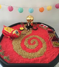 Chinese New Year  We've had so much fun with this tuff tray. It's simply 4kg bags of red dyed rice and about 3kg of gold painted chickpeas,  (i'm really impressed with how these turned out!)  Some sparkly pipe cleaner noodles, pompom balls, a beautiful golden temple from TTS Group, and a lovely Chinese dragon puppet that my Dad bought back from his holiday in Hong Kong. Even all messy the red and gold look very lovely, and so inviting to play with