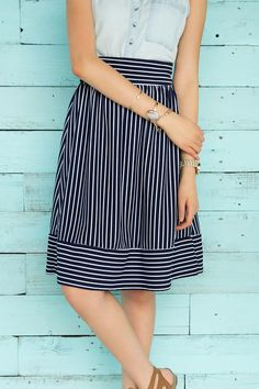 """Swing into summer with the Alyce Striped Midi Skirt. This a-line skirt boasts navy & white stripes with an exposed zipper at the back. Style with a chambray tank or a white blouse for a polished look.<br /> <br /> - 26"""" length<br /> - 28"""" waist<br /> - 33"""" sweep<br /> - measured from a size small<br /> <br /> - 95% Polyester, 5% Spandex<br /> - Hand Wash<br /> - Made in U.S.A."""
