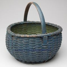 """PAINTED VALLEY OF VIRGINIA WHITE OAK SPLINT ROUND BASKET,  nicely woven bulbous form with a wrapped rim, kick-up base, applied foot, and arched handle with carved rim notch supports. Original dry blue-painted exterior and green-painted interior. Probably Pulaski/Craig/Giles Co. area. 1890-1920. 12"""" HOA, 6 1/2"""" H rim, 12"""" D rim. <BR><I>Outstanding condition with minor loss to foot wrap only.</I><BR>Literature: Parallels Shaw - American Baskets, p. 168.<BR> Provenance: Purchased at an estate…"""