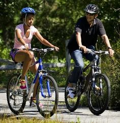 Celebrities on Bikes: US President Barack Obama and his daughter Malia ride bikes in Manuel F. Correllus State Forest
