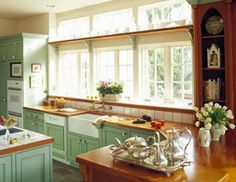 Wide window with transom windows and interesting and herb shelf. Here, a deep sill is repeated with a narrow shelf hung between the casement windows and transom windows. The collection of glass bottles on the shelf accentuates the sunlight shining in. Kitchen Window Shelves, Kitchen Window Sill, Kitchen Cabinets, Kitchen Windows, Glass Shelves, Green Cabinets, Cupboards, Kitchen Paint, New Kitchen